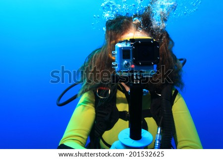 Scuba woman with action camera underwater in the sea  - stock photo