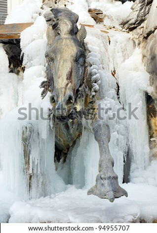 Sculpted horse coming out of ice, detail of the frozen Bartholdi fountain at the place des terreaux, Lyon, France. - stock photo