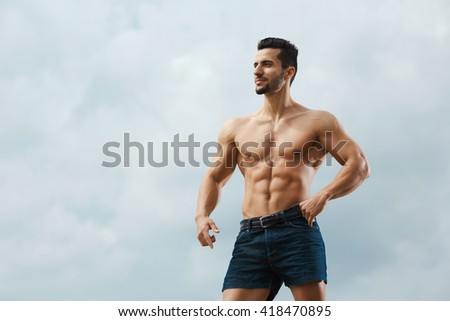 Sculpted perfection. Handsome shirtless muscular male standing outdoors looking away. - stock photo