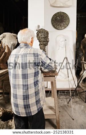 Sculptor rear view workshop scene - stock photo