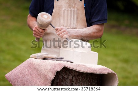 Sculptor working a block of stone with a chisel - stock photo
