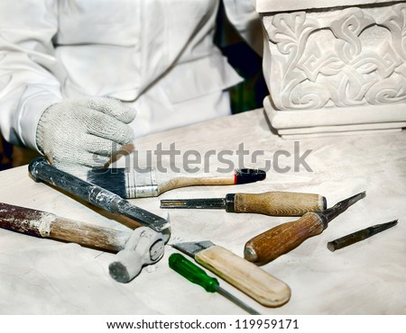 Sculptor working in the workplace, where many different tools - stock photo