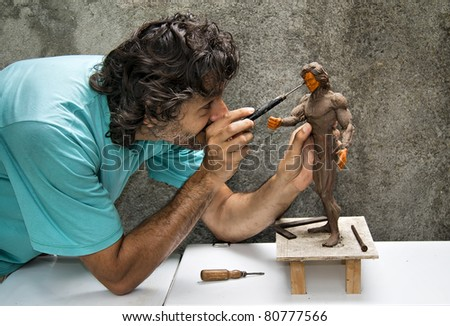 sculptor working on a human figurine in clay - stock photo