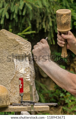 sculptor working on a stone sculpture - stock photo