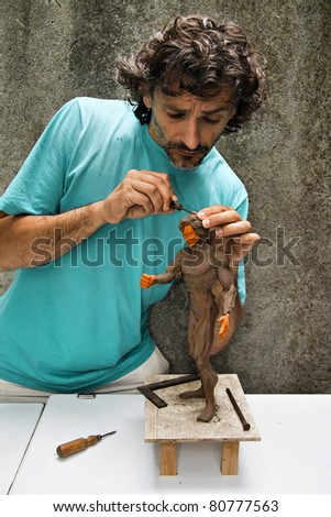 sculptor works on  a human figurine