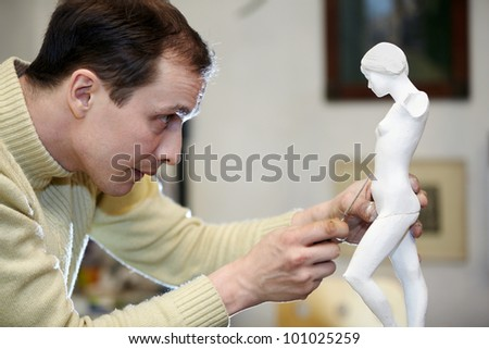 Sculptor works with concentration in the studio on a fragment of plaster sculpture. - stock photo