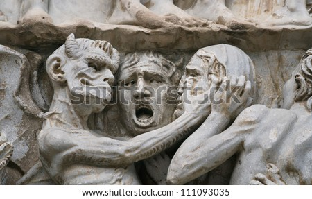 Sculptural group with the image of a devil and sinners on an external facade of the Cathedral, Orvieto, Italy - stock photo
