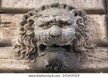 Sculpture of a lion's head on a historic building in Italy
