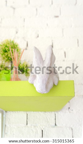 Sculpture of a Realistic White Rabbit as Interior Decoration on a neon green shelf, Selective Focus, Abstract Blur Brick Background  - stock photo