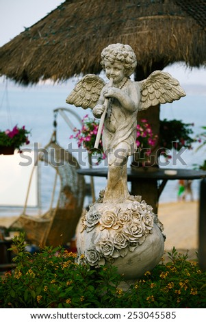 Sculpture of angel stand on quay with sea view and wickerwork swing - stock photo