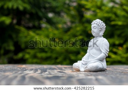 Sculpture of Buddha become enlightened on green background. Yoga and meditation concept - stock photo