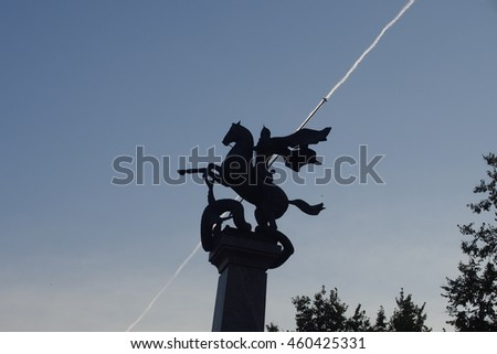 Sculpture of St. George with a spear. Aircraft contrails.