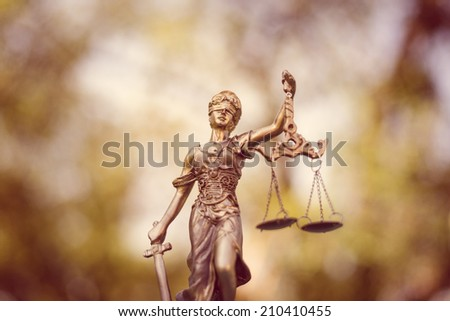 sculpture of themis, femida or justice goddess on green leaves natural bokeh background - stock photo