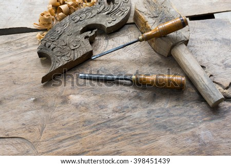 Sculpture tools and wood chips spread on the wooden table, what seems to be the carver's workplace. - stock photo