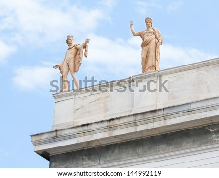 Sculptures of Apollo and Hera on the roof-top above the entrance of the National Archaeological Museum of Athens in Greece. - stock photo