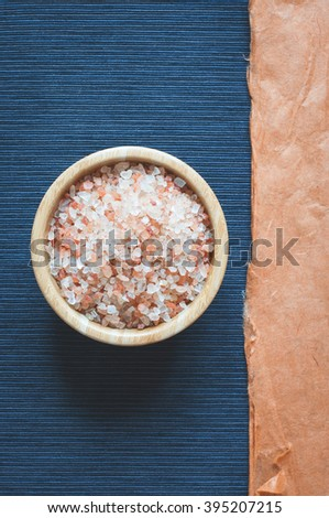 Sea aromatherapy bath salt on dark blue background. Top view. Space for text. Low contrast toned - stock photo