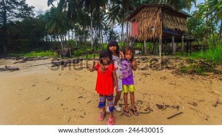 Sea Bajau children posing in front of their traditional house. Shallow dof, selective focus on the face of the children.