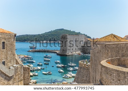 Sea bay with boats at the fortress.Bright sea and the sky over the bay.The ancient fortress by the sea.Many yachts in the city port.Image of boats without any identification marks, claiming ownership.