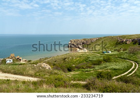 Sea bay with rocky shore, stones, grass, fisherman's huts, round dirt road - stock photo