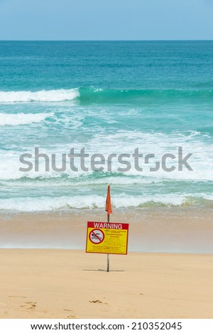 Sea beach with warning flag for swimming - stock photo