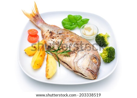 Sea bream fish with potato on white plate - stock photo