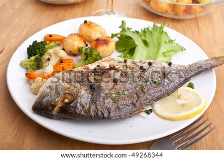Sea Bream fish with vegetables on white plate close-up - stock photo