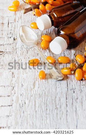 Sea buckthorn oil in a bottle and fresh sea buckthorn on a white wooden background. Alternative medicine. Copy space background. Selective focus - stock photo
