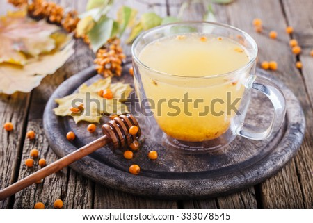Sea buckthorn tea for health.Autumn still life on wooden background. - stock photo