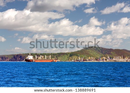 Sea cargo vessel accompanied by pilot boats goes to the port terminal for unloading - stock photo