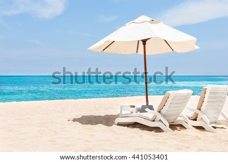 Sea chairs and umbrellas on the sand near blue water side with horizon and clear sky - stock photo