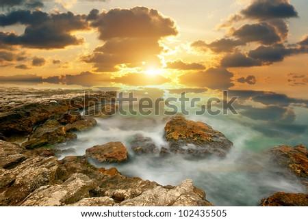 Sea cliffs on the bright sunset - stock photo