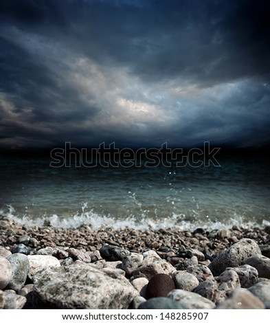 sea coast, stones, waves and dark dramatic stormy sky landscape - shallow DOF