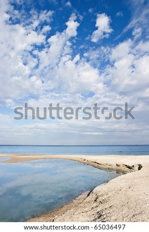 Sea coast with beautiful clouds - stock photo