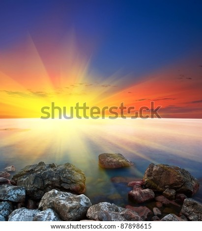 sea coast with stones at the sunset - stock photo
