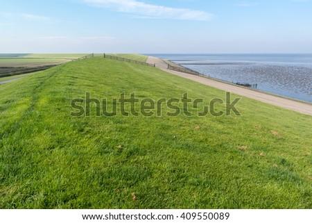 Sea dyke between Frisian polders and Wadden Sea - coastline of Friesland, Netherlands - stock photo