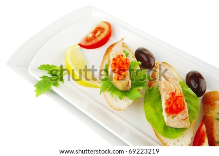 sea fish food : small salmon sandwiches served with caviar and olives isolated over white background