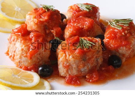 sea fish in tomato sauce with olives on the plate closeup horizontal