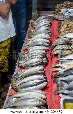 Sea Fishes on display in a sea food stall and customer awaiting their orders