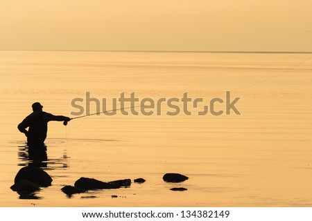 Sea flyfishing in the sunset - stock photo
