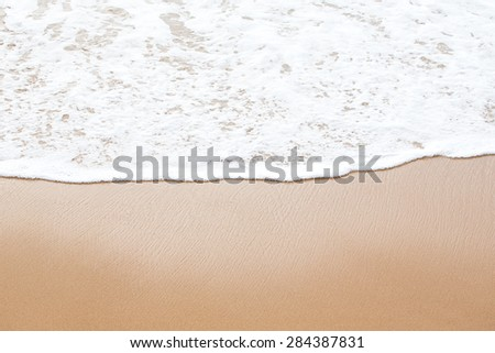Sea foam on a sandy beach. - stock photo
