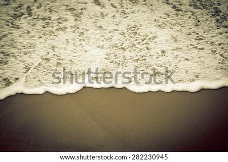 Sea foam on a sandy beach. Toned. - stock photo