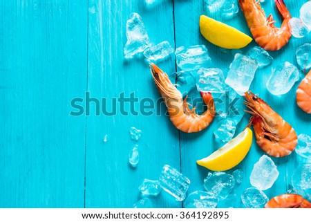 Sea food background, whole prawns, lemon and ice - stock photo