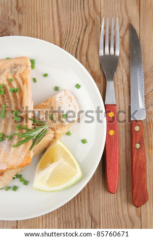 sea food : roasted pink salmon fillet with chinese onion, cherry tomatoes pieces, pepper grinder, rosemary twigs and lemon on wooden board