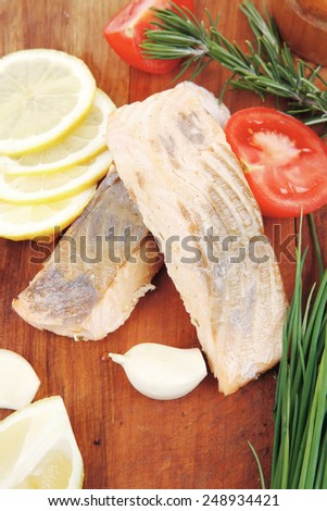 sea food : roasted pink salmon fillet with chinese onion, cherry tomatoes pieces , rosemary twigs and lemon on wooden board isolated over white background