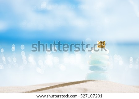 sea glass seaglass with golden crown on glitter  seascape background, shallow dof