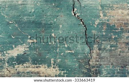 Sea green broken cracked brick wall. - stock photo