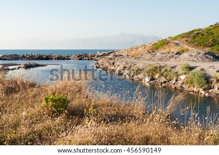 Sea harbor with blue water and green hills - stock photo