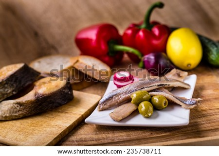 Sea herring with garnish on wooden plate an smoked fish. - stock photo