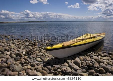 Sea-Kayak on coast with lots of stones. Jutland, Denmark - stock photo