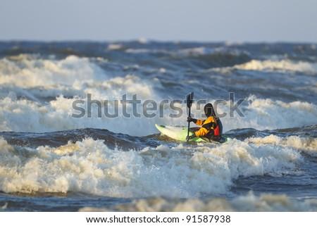 Sea kayak on stormy waves. - stock photo